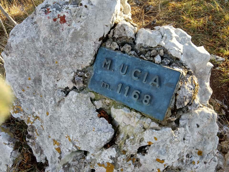 Il sentiero di salita percorre la sommità del Monte Ucia identificata da questa targa metallica